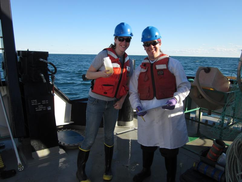 Skylar Carlson and a scientist from Dr. An Li's lab holding a sample of bacterioplankton on board the RV Lake Guardian.