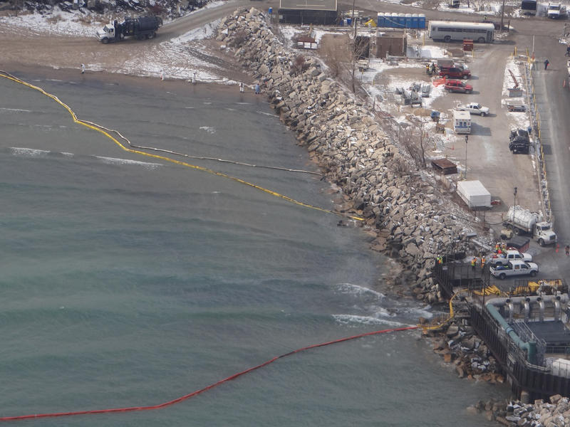 Cleanup crews work to deploy a containment boom along the Lake Michigan shoreline near the BP Whiting Refinery in Whiting, Ind., March 25, 2014, to recover crude oil discharged from the refinery.