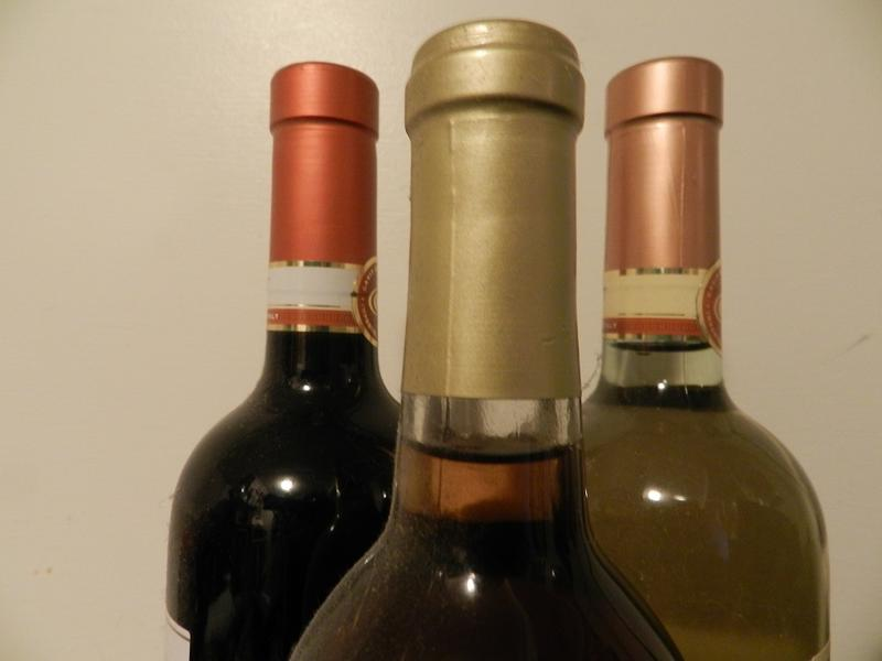 Three wine bottles from the neck up.