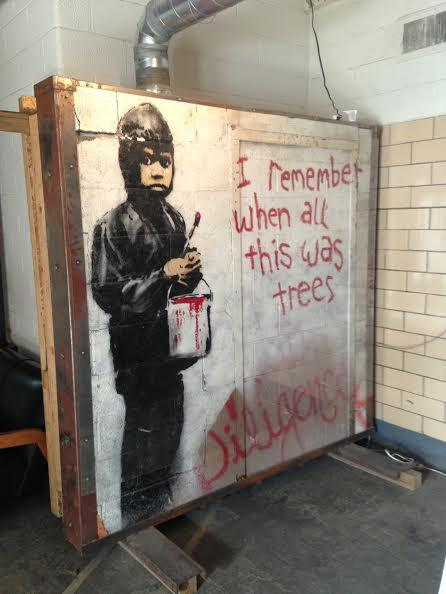 The piece sits in the 555 Gallery in Detroit. Widely believed to be by Bansky, now two Detroiters say they did it.