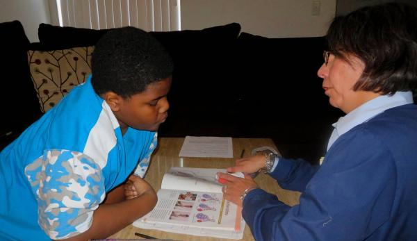 Mary Kim helps Jovon White take his asthma medication.