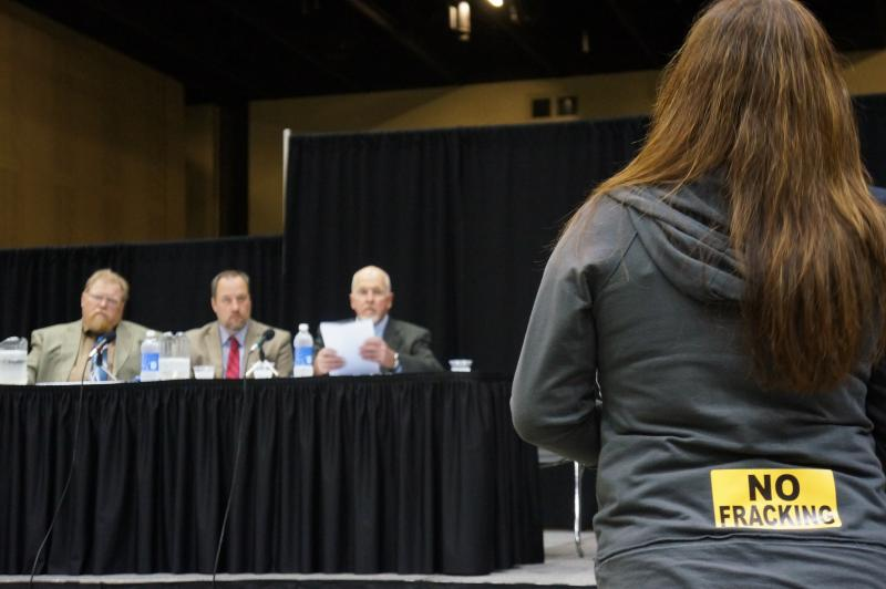 "Member of the public with a ""No Fracking"" sticker on her clothes as she testifies before a panel of environmental regulators."