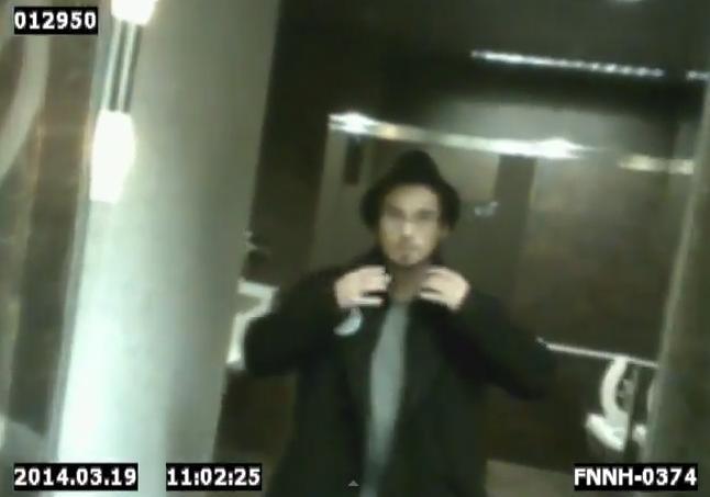 Spy glasses wearer checks his specs in the bathroom.