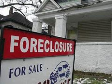 "A photograph of an old white house with sign out front reading ""Foreclosure"" and ""For Sale."""