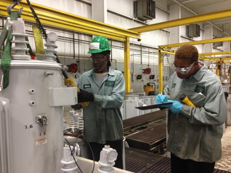 Tyrone Powe (left) shows one of the trainees how to work with an old DTE transformer. He is 67 years old.