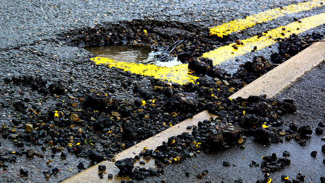 A crumbling road with a large pothole in the asphalt