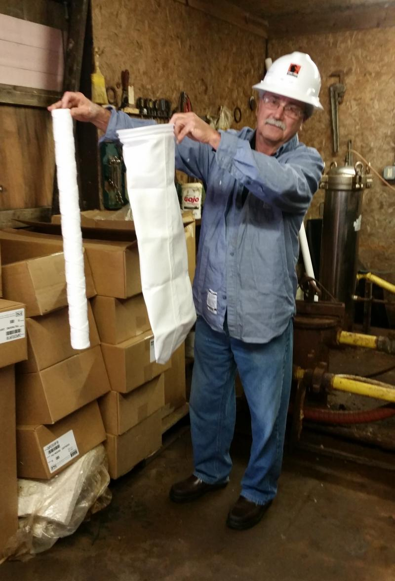 Stallion Operations Manager Randy Ile holds up 25 and 10 micron filters, showing how they clean the wastewater before sending it down the well.