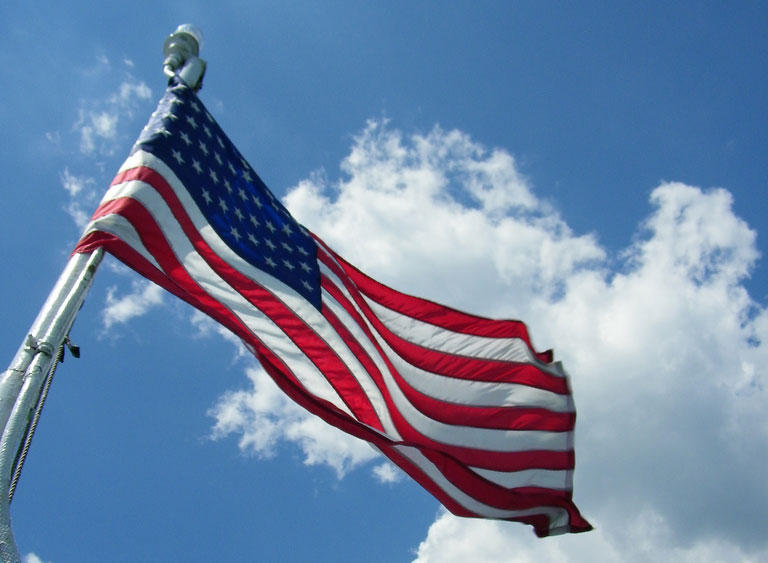 American flag fluttering against a blue sky