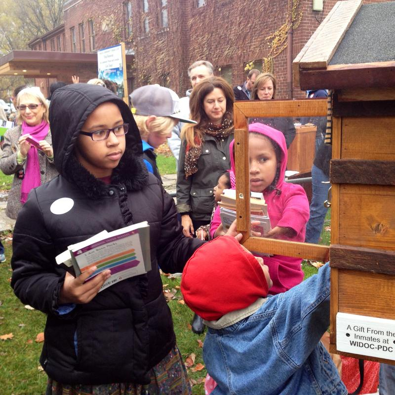 Gwen Vaughn, 10, on the left, helps her brother Henry put books into her neighborhood's new Little Free Library.
