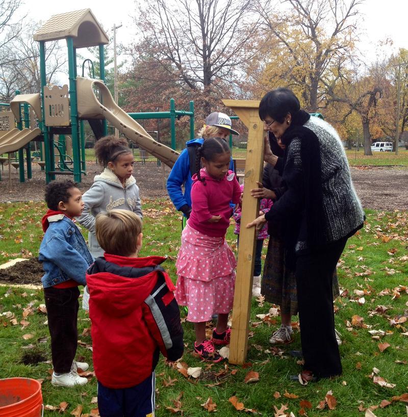Neighborhood kids help Marsha Bruhn plant the new Little Free Library