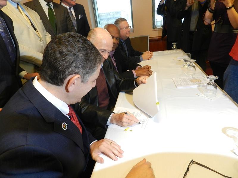 Lansing Mayor Virg Bernero (foreground), developers Frank Kass and Joel Ferguson sign an agreement in November 2014.