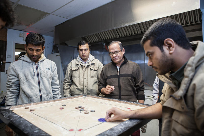 A group of Bangladeshi men play Carrom board at Bismillah Grocery, in Hamtramck.