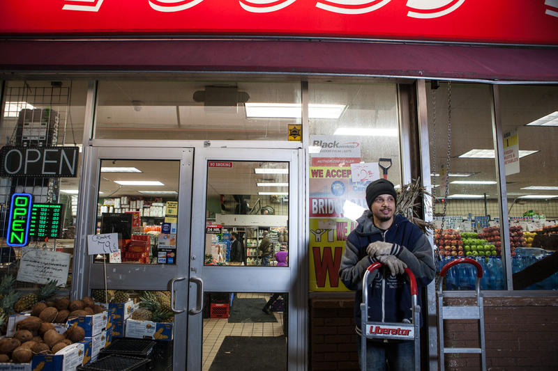 A young man takes a break from stocking produce at an International grocery store in Hamtramck.