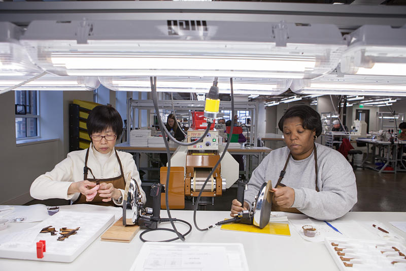 Li Leung and Myra Mosley work on leather paint and finish at Shinola in New Center.
