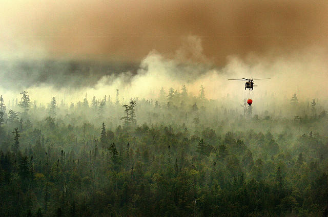 a helicopter flies over a wildfire