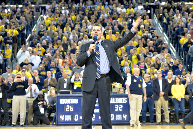 Jim Harbaugh greets the crowd at a U of M basketball game on December 30, 2014.