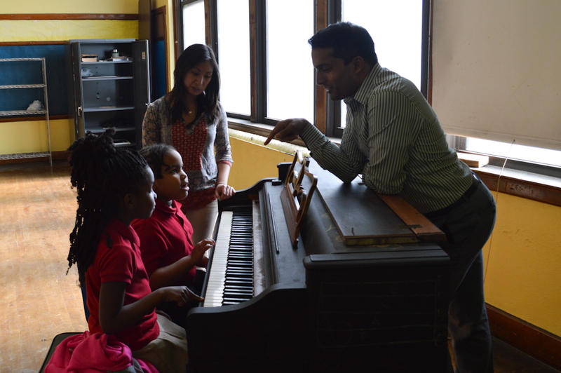University of Michigan students teach kids piano at Woodbridge Community Center.
