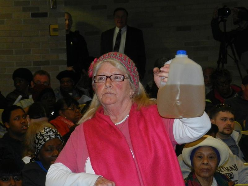 A Flint resident holds a jug of tainted Flint water.