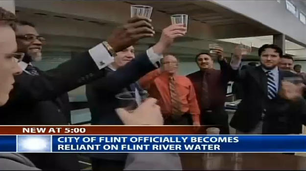Flint officials toast each other as they flip the switch to the Flint River.
