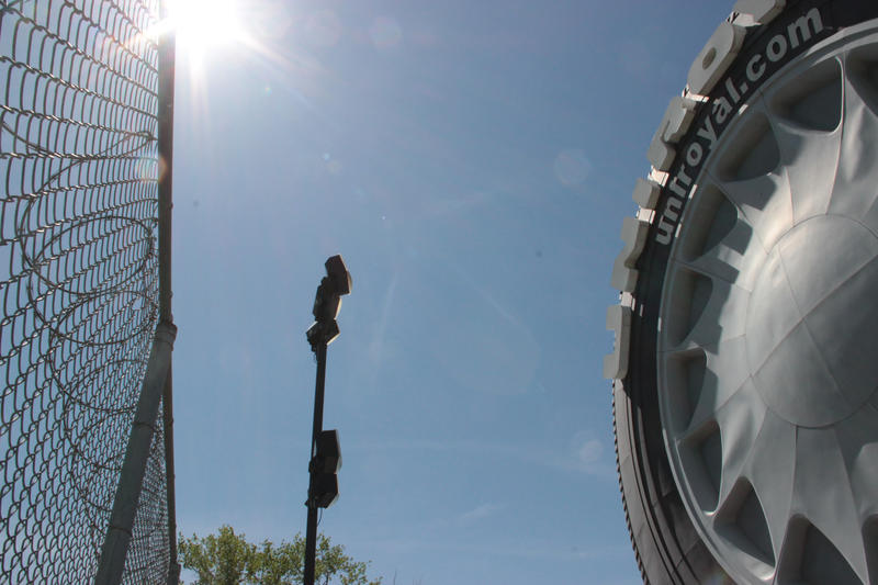 The 12-foot high fence and the razor wire suggests the tire is a desirable destination to the univited.