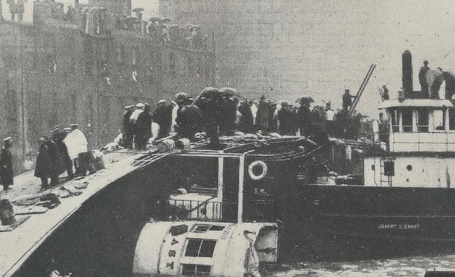 Passengers stand atop the capsized boat