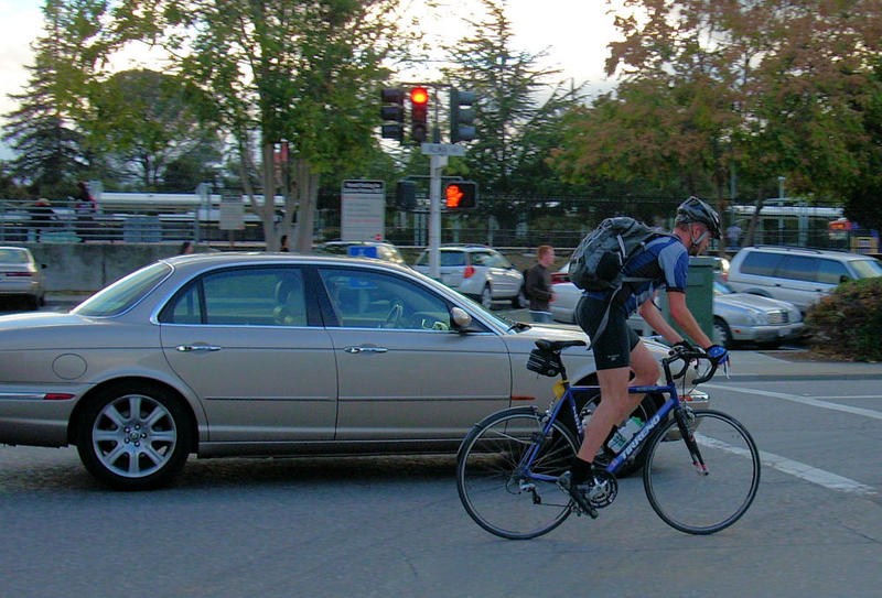 car and bicyclist riding side by side in the road