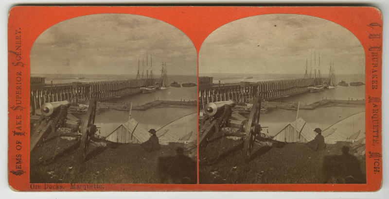 """Ore docks. Marquette."" Stereograph by Brainard F. Childs, ca. 1873.  Childs extensively documented the mining activities and natural beauty of the Lake Superior region. The shadow of the photographer and his camera appear lower right."