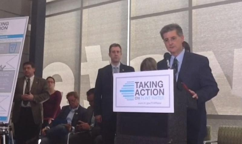 "Many media outlets are livestreaming the press conference. Here is MDEQ Director Dan Wyant speaking at a podium with a ""taking action"" sign affixed."