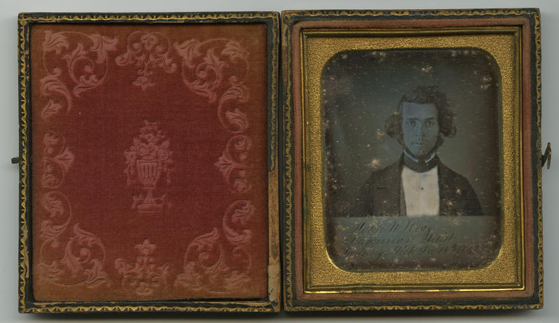 """John W. Hoag, Daguerrean Artist, Lansing, Mich., Dec. 14th, 1849."" This daguerreotype self-portrait with sign-board indicates the sitter's profession. Likely the earliest known portrait of a Michigan photographer."
