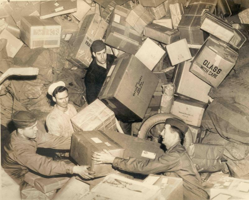 U.S. troops almost buried by parcels do their best to handle the holiday mail, ca. 1944