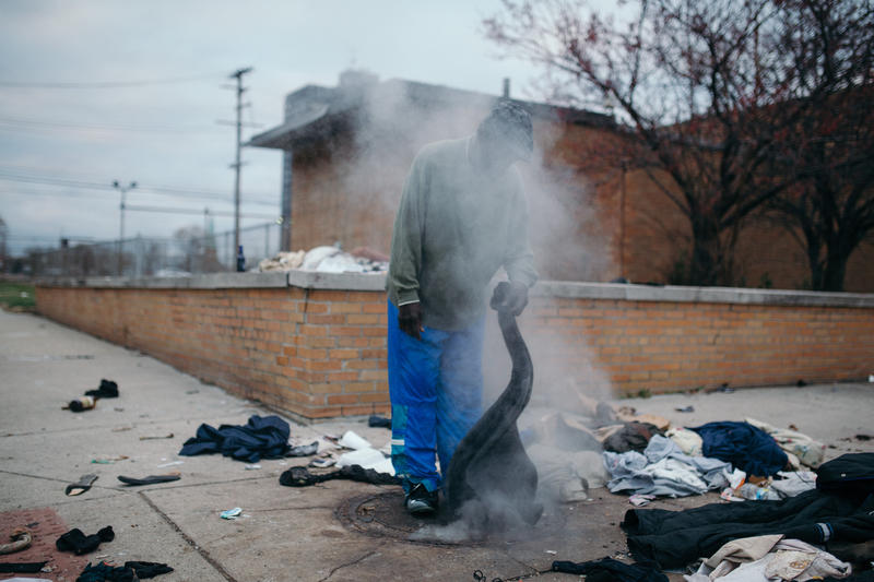 A homeless man warms his jacket using a steam vent at the intersection of 8th and Fort St.