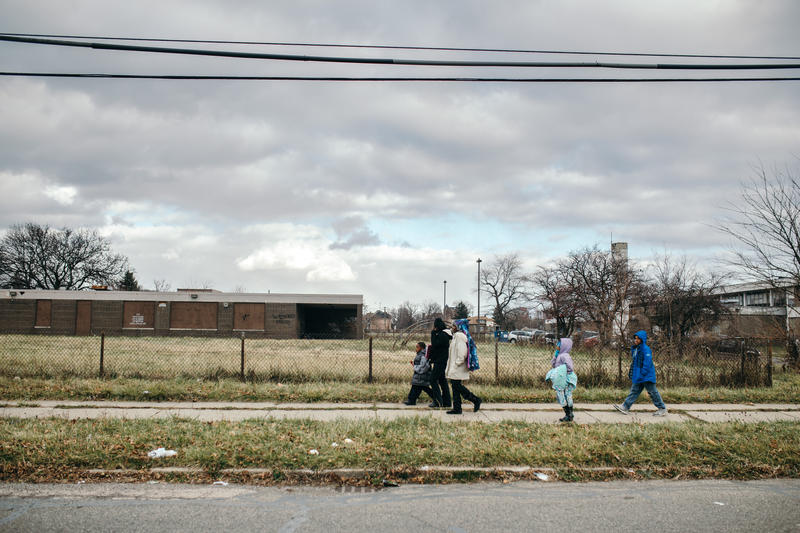 A group of students pass an abandoned school as they walk home from school.