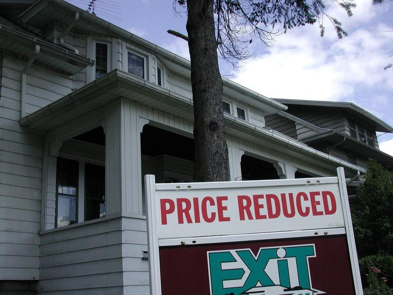 """Price Reduced"" sign in front of home."