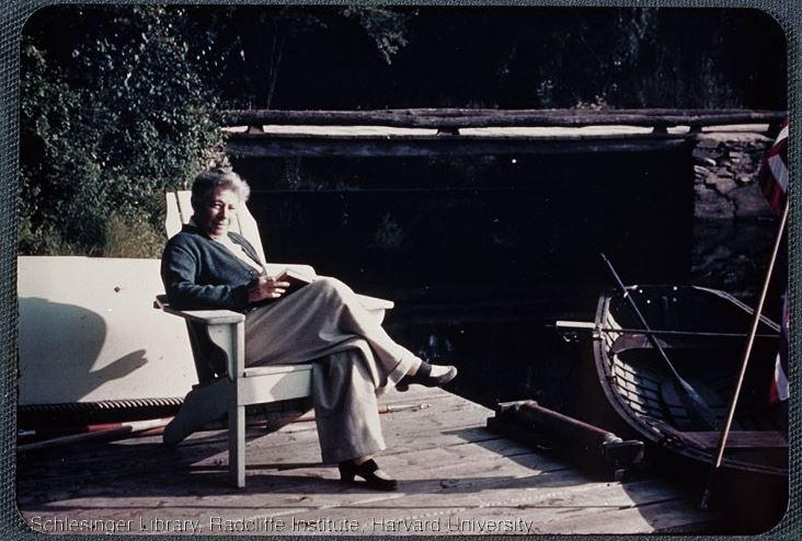 Frances Kellor reading on a dock