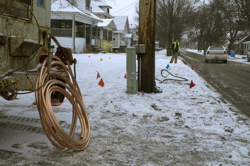 A copper service line will replace a lead service line on this residential street in Lansing. In the background is a sample lead service line that's been removed.
