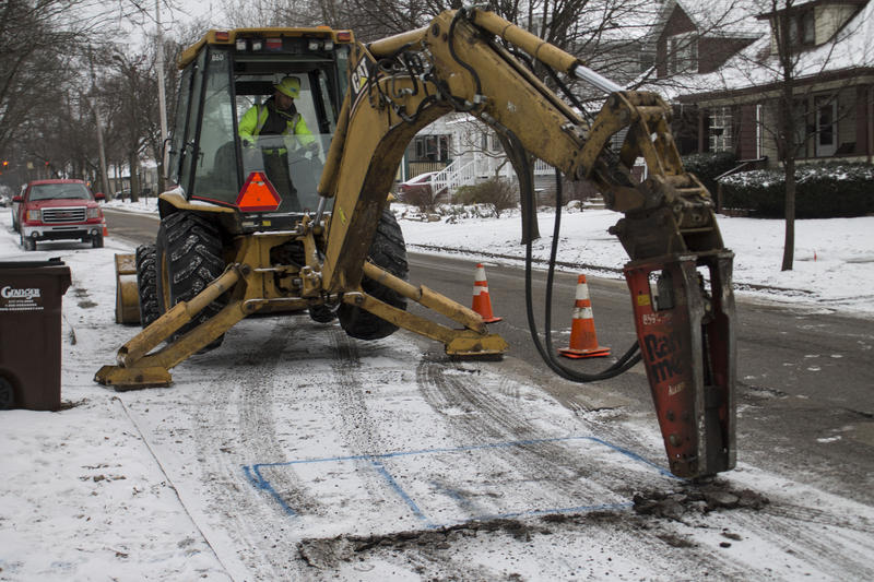 With a jackhammer, a crew member in Lansing begins digging a hole toward a lead service line.