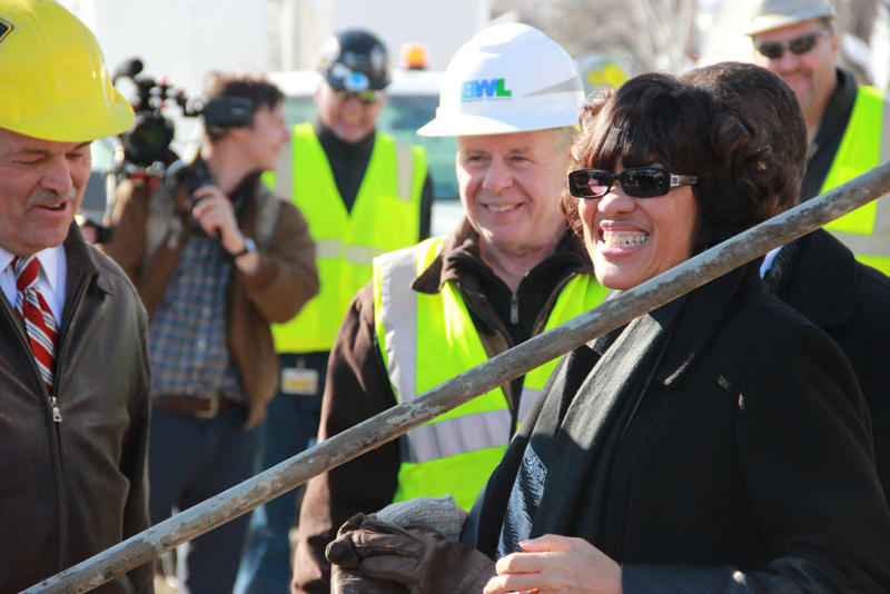 Flint Mayor Karen Weaver (right) stands next to the lead drinking water line that was pulled from a home in Flint.