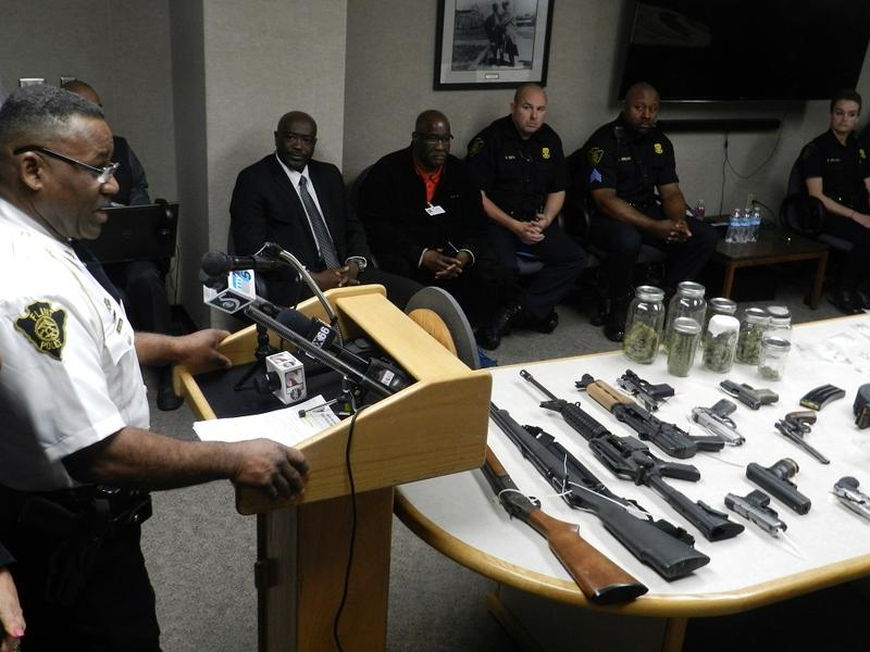 Flint Police Chief Timothy Johnson stands before a table strewn with guns, drugs and thousands of dollars of cash seized during recent arrests