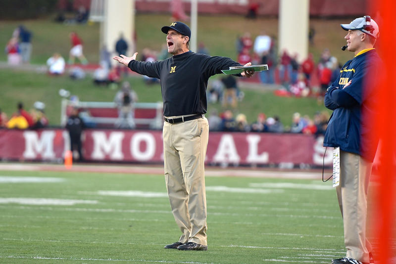 Michigan coach Jim Harbaugh, arms out, protesting a call