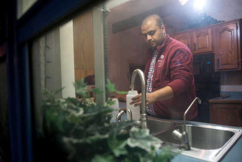 Anurag Mantha, a doctoral student in civil and environmental engineering, fills a water sample bottle in a Flint resident's kitchen earlier this year.