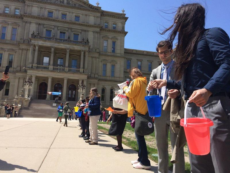 Activists form a bucket brigade to carry water from the state Capitol.