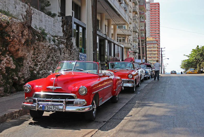 Classic American cars line the street waiting to take visitors for a ride.