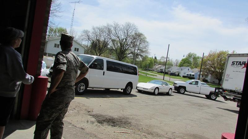 Michigan National Guardsmen watch as a truck carrying pallets of bottled water drives away from Fire Station #8.