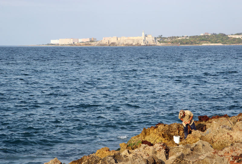 Man fishing off the rocks near the seawall with the Morro fortress in the background.