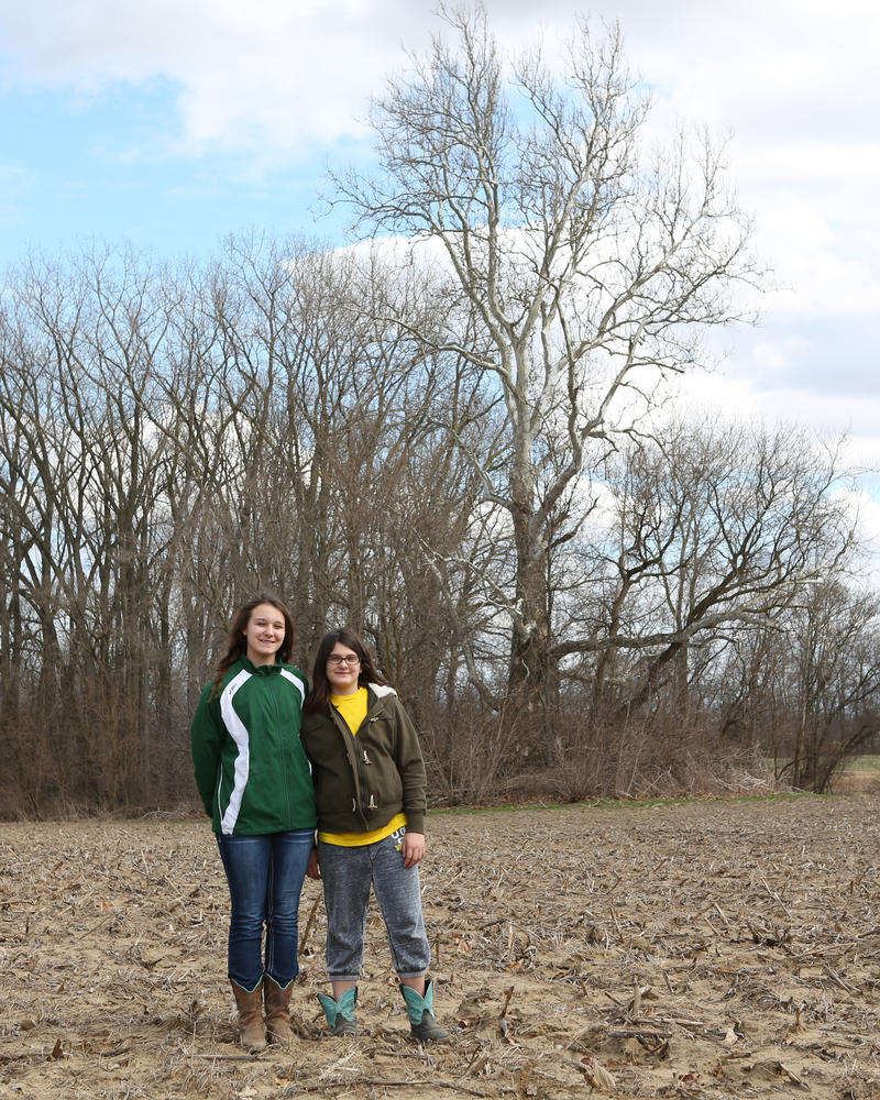 Kindell Covey, left, and her sister Denae Covey stand in a field in front of the giant sycamore