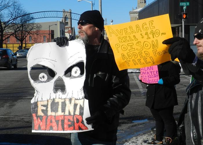 A man protests the poor quality of Flint's water