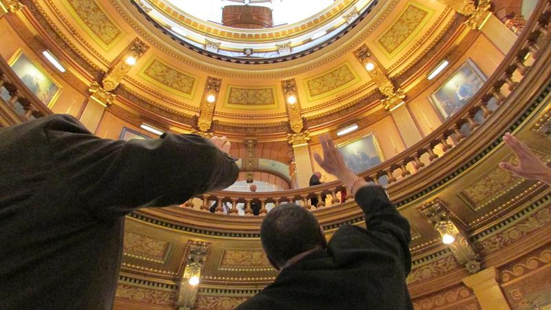 Beneath the state Capitol dome, Flint pastors raise their hands to the heavens in prayer.
