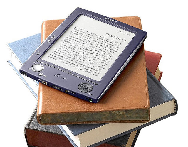 an e-reader on top of a stack of books