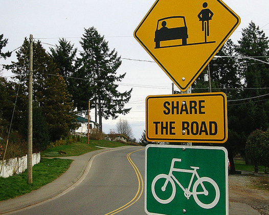 "A road sign says ""Share the road"" for bicycle safety."