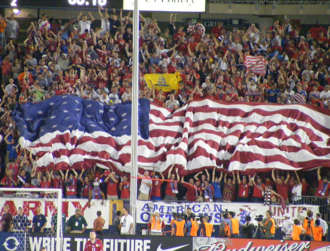 Fans hold up a flag in support of the U.S. Men's National Team.